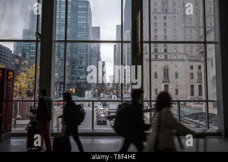 TORONTO, CANADA - NOVEMBER 13, 2018: People rushing in a lobby of union station in front of the panorama of York street surrounded by skyscrapers in t - Stock Photo