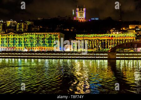 France, Rhone, Lyon, historical site listed as World Heritage by UNESCO, St Jean Cathedral, the courthouse at the edge of Saone River and Notre Dame de Fourviere Basilica during the Fete des Lumieres (Light Festival), show Reflets of Damien Fontaine on the hill of Fourviere - Stock Photo