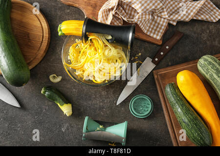 Fresh zucchini spaghetti with spiral grater and vegetables on dark table - Stock Photo
