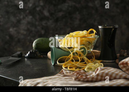 Fresh zucchini spaghetti in bowl with spiral grater on dark table - Stock Photo