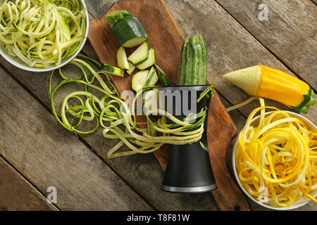 Fresh zucchini spaghetti with spiral grater on wooden table - Stock Photo