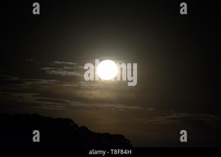 Bright moonlight from full moon rising with thin wispy clouds as backdrop - Stock Photo