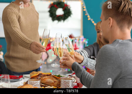 Happy family clinking glasses during Christmas dinner at home - Stock Photo