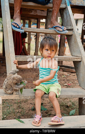 Boca de valeria, Brazil - December 03, 2015: child feeding sloth with green leaves on wooden stairs. Poverty and childhood concept. Human and wildlife - Stock Photo