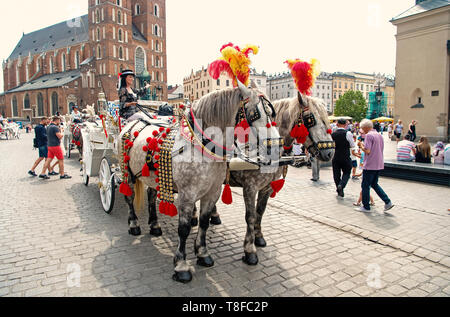 Krakow, Poland - June 04, 2016: girl rider invite to horse carriage ride in city square. Vacation, tour, travelling, discovery concept - Stock Photo