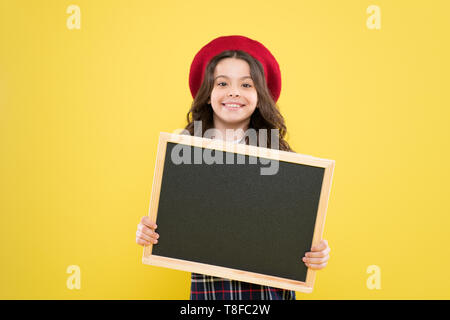 small girl in french beret. advertisement. child with empty blackboard. parisian child on yellow background. happy girl with curly hair in beret. your advertisement in good hands. advertisement board. - Stock Photo