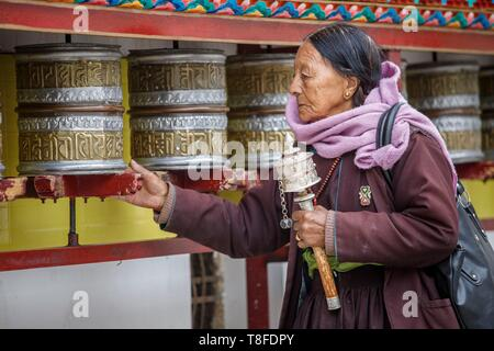 India, state of Jammu and Kashmir, Himalayas, Ladakh, Indus Valley, Leh (3500m), annual Ladakh Festival, Buddhist temple of Gompa Soma (Chokhang), an elderly woman walks around the temple in a clockwise direction while turning the prayer wheels - Stock Photo