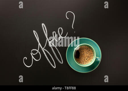 An overhead photo of a cup of coffee on a black background with chalk lettering and copy space - Stock Photo