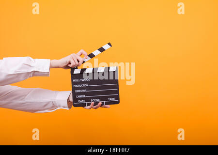 Shot of isolated hands on yellow background holding a clapper. Teenage girl holding clapper in studio. - Stock Photo