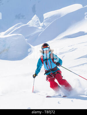 Female freeskier skiing in backcountry on fantastic Monte Rosa glaciers - Stock Photo