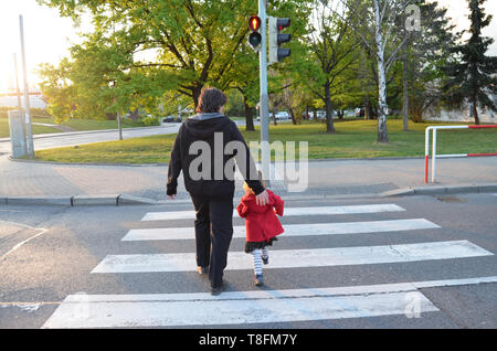 A man and a small child on a zebra crossing trespassing by crossing  the street on red flashing lights. Father is wearing black clothes, the girl has  - Stock Photo