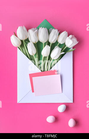 White tulips in paper envelope with blank paper cards and Easter eggs on vibrant pink background - Stock Photo