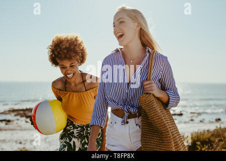 Two young women walking with a ball and bag along the beach. Female friends going on picnic at beach.