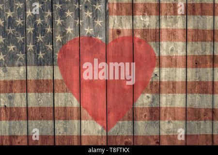vintage american flag with a heart painted on the side of an old weathered barn - Stock Photo