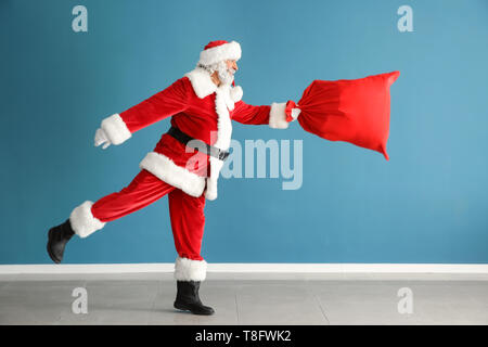 Santa Claus with bag full of gifts against color wall - Stock Photo