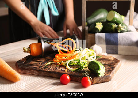 Fresh zucchini and carrot spaghetti with spiral grater on wooden table - Stock Photo
