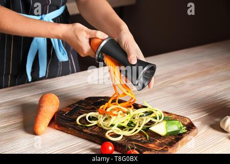 Woman making zucchini and carrot spaghetti - Stock Photo