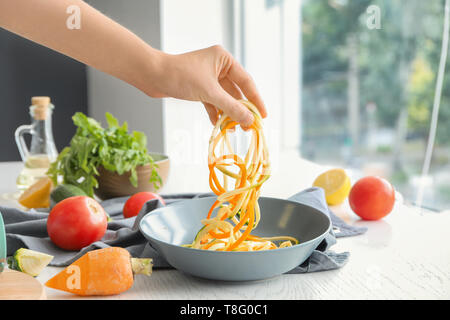 Woman holding fresh zucchini and carrot spaghetti over bowl - Stock Photo
