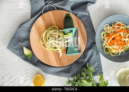 Fresh zucchini spaghetti with spiral grater on light table - Stock Photo