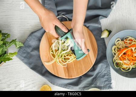 Woman making zucchini spaghetti - Stock Photo