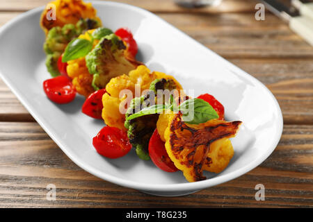 Tasty grilled cauliflowers with tomatoes on plate - Stock Photo