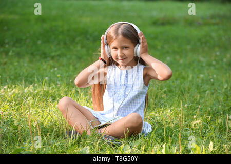 Cute little girl listening to music in park on summer day - Stock Photo