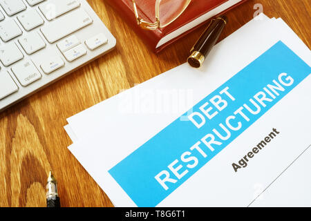 Debt restructuring Agreement DRA with keyboard and pen. - Stock Photo