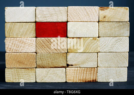 Stand out from the crowd concept. Red wooden block and whites.