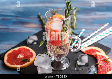 Fresh grapefruit cocktail with rosemary in glass cup on slate plate - Stock Photo