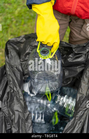 Separate garbage collection. Hand putting plastic bottle into black plastic trash bag filled with other bottles. Stock Photo