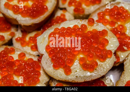 Sandwiches with butter and red caviar on a plate closeup - Stock Photo