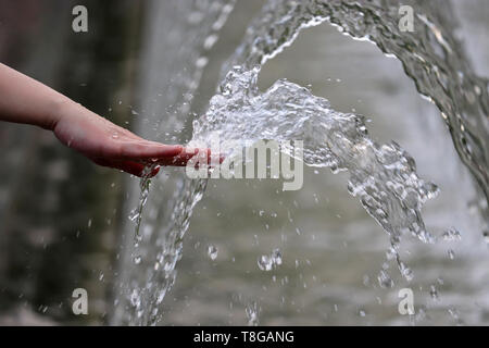 Freshness and cool, female hand in a water of the fountain. Girl playing with splashing jets, concept of humidity, hot summer weather - Stock Photo