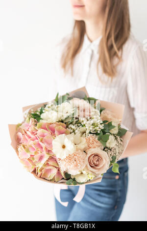 Delicate bouquet of mixed flowers in womans hands. the work of the florist at a flower shop. Delicate Pastel color. Fresh cut flower. White and pink - Stock Photo