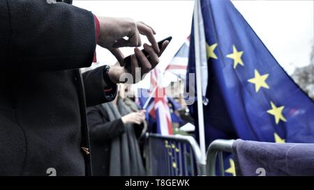 Man holding a mobile phone next to an EU flag during Brexit protest and EU elections. - Stock Photo
