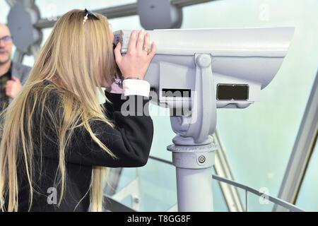 Blond girl looks through telescope, blond girl holding telescope. blond girl wearing black jacket, girl wearing black jacket looks through telescope. - Stock Photo