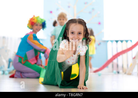 Children kids playing with clown on birthday party in entertainment centre. Child girl climbing through tunnel - Stock Photo