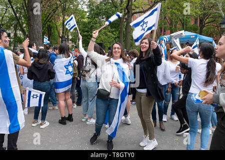 An Israeli & American young lady dance happily at the Israel Independence Day celebration in Washington Square Park in Manhattan,  NYC. - Stock Photo