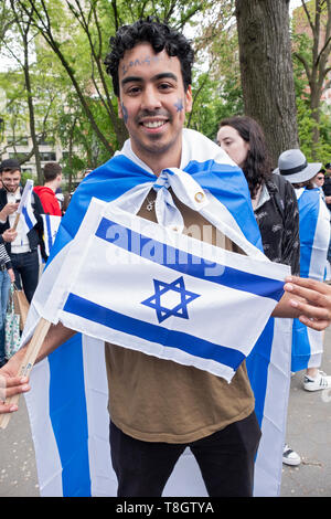 Posed portrait of an NYU student who is wearing & holding an Israeli flag. At the Israel Independence Day celebration in Washington Square Park, NYC - Stock Photo
