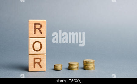 Wooden blocks with the word ROR and coins. High level of business profitability. Return on investment, invested capital, rate. Success. Growth. Profit - Stock Photo