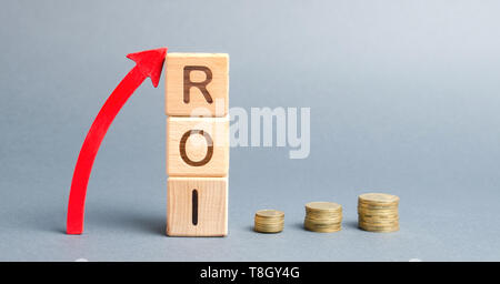 Wooden blocks with the word ROI and arrow up. High level of business profitability. Return on investment, invested capital, rate. Success. Growth. Pro - Stock Photo