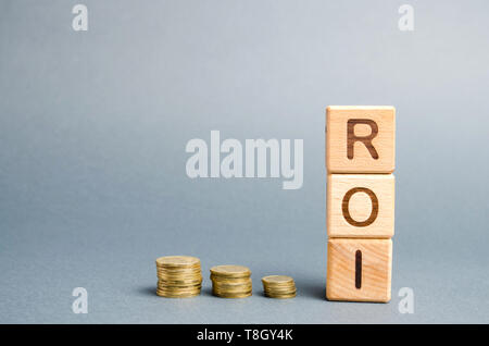 Wooden blocks with the word ROI and coins. High level of business profitability. Return on investment, invested capital, rate. Success. Growth. Profit - Stock Photo