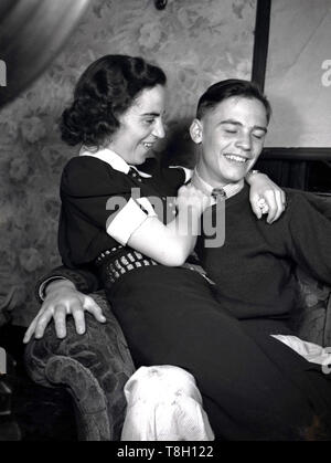 1950s, historical, a happy young couple in love.....a young man sitting indoors on a sofa chair with his girlfriend on his lap and with her arms around him, Manchester, England, UK. - Stock Photo