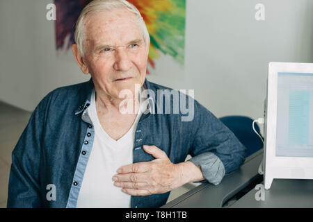 Senior man feeling chest pain- indicator of a possible heart attack - Stock Photo