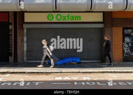Belfast 13th May 2019. A Man Sleeping rough on Castle street, Belfast, while members of the public walk past. - Stock Photo
