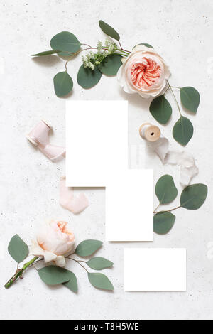 Wedding stationery, birthday mock-up scene. Blank greeting cards, silk ribbons, eucalyptus leaves and blush pink English roses flowers. White concrete - Stock Photo