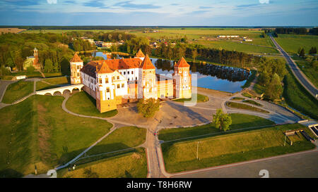 Aerial view of Medieval Mir castle complex on sunny spring day. Famous landmark, UNESCO world heritage. Drone panorama of Mirsky zamok, Belarus - Stock Photo
