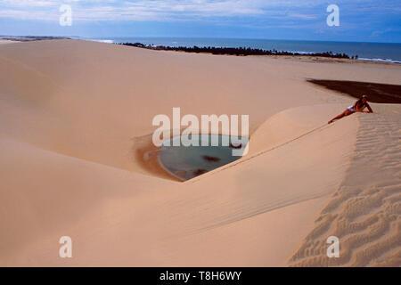 Brazil: A woman lying on the sand dune near Jericoacoara in Ceara - Stock Photo