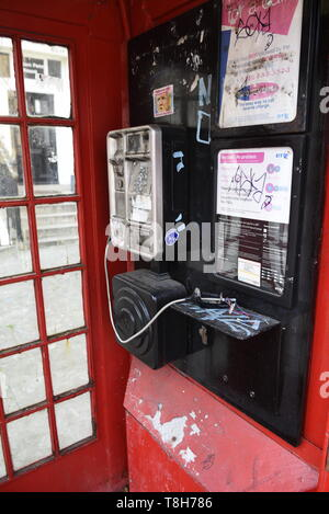 Traditional red London telephone box that has been vandalised, London. - Stock Photo