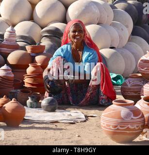 Smiling attractive mature woman sitting on ground surrounded by traditional round clay pots she is selling in Pushkar, Rajasthan, India - Stock Photo