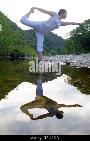 Woman performing yoga on a rock in a mountain river - Stock Photo